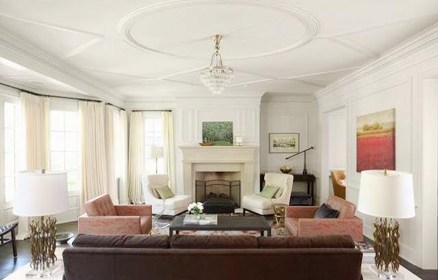 Living room with white moulded ceiling, a crystal ceiling medallion, a dark brown couch, patterned area rug, a dueling brick armchairs, a dark wood coffee table, a molded fireplace with two white armchairs next to it