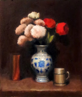 Oil painting of plastic apricot-coloured dahlias and red roses in a blue and white porcelain vase, with a mug on one side and a copper vase on the other.