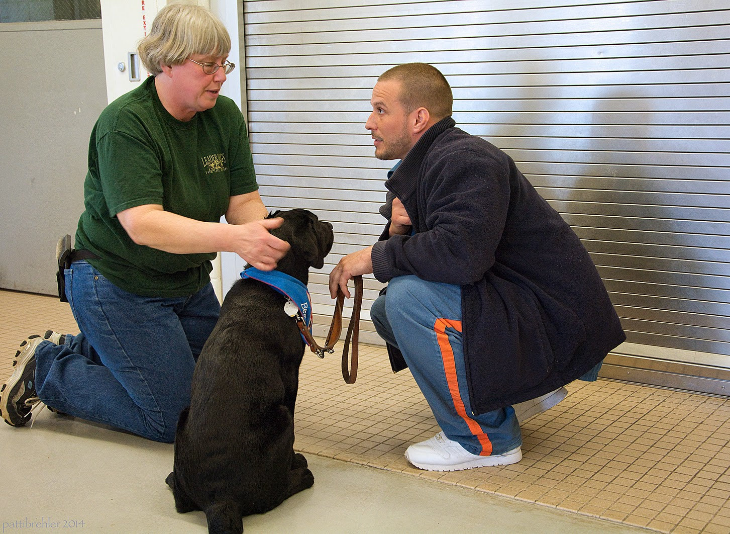 A woman dressed in a short sleeved green t-shirt and blue jeans wearing glasses and has short white hair is kneeling on the left. Her hands are checking the ears of a young black lab puppy, who is sitting on the cement floor facing away from the camera. A man is squatting to the right of the puppy. He is wearing a dark blue fleece jacket and the blue prison pants and white tennis shoes. He is holding the brown leather leash of the puppy with his left hand, which is leaning on his knee. He is looking at the woman and listening to her talk.