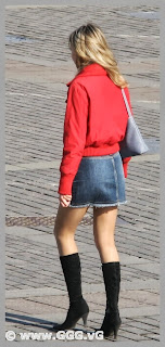 Girl in jean skirt and red jacket on the street