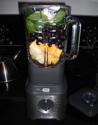 image blender holding Mango,Banana,Blueberries,Spinach