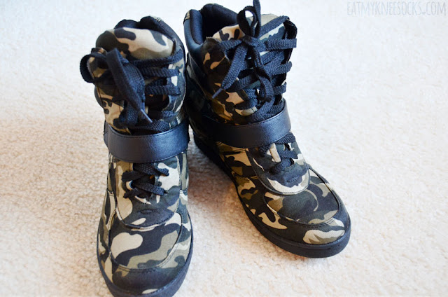 Close-up of the faux leather black camouflage-print sneaker wedges from AMIClubwear.