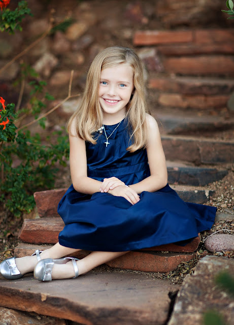 Tucson child sits on rocky steps in family backyard wearing a blue party dress