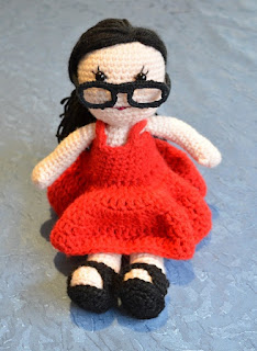 Front view of Kwokkie Doll seated, as she looks over the rims of her glasses.