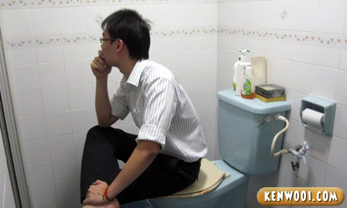 sitting on toilet bowl
