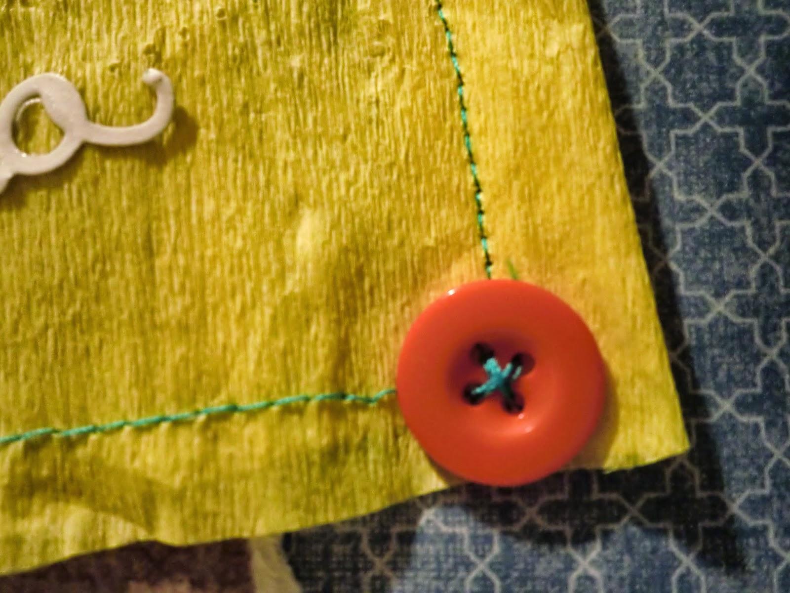 Detalle del cosido y el botón naranja