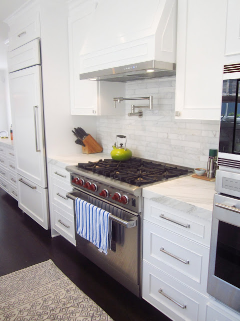 close up of stainless steel appliance oven with stove and white panel hood