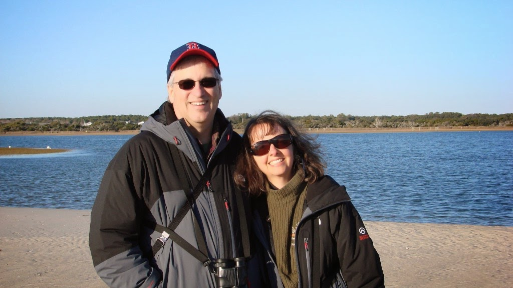 Joe and Karen smile at camera while standing in front of a large lake on a sunny day