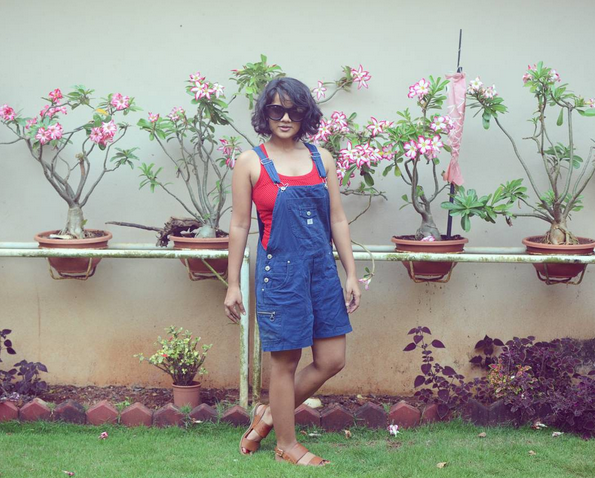 Dayle Pereira blogger at Style File showcases her dungarees and tank top outfit in front of a flower wall on social media channels