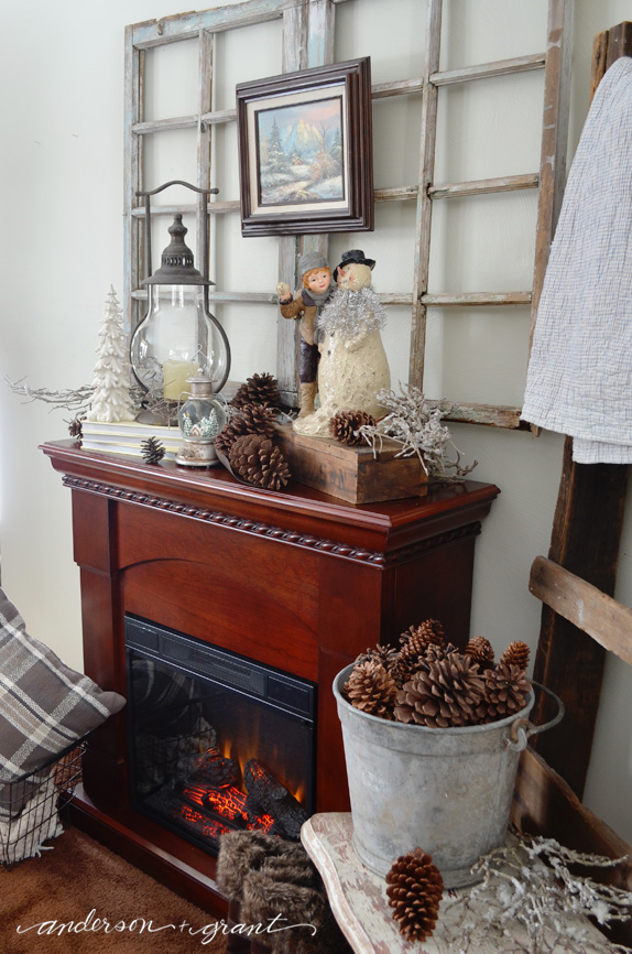Keeping out Christmas decorations to create a beautifully decorated fireplace mantel for winter. | anderson + grant