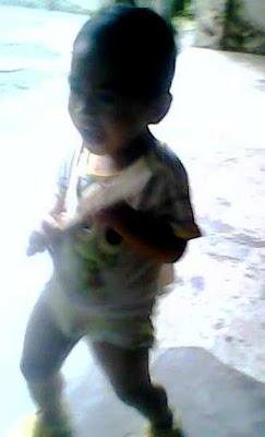 +foto anak kecil yang mempraktekkan gaya gitaris rock ternama