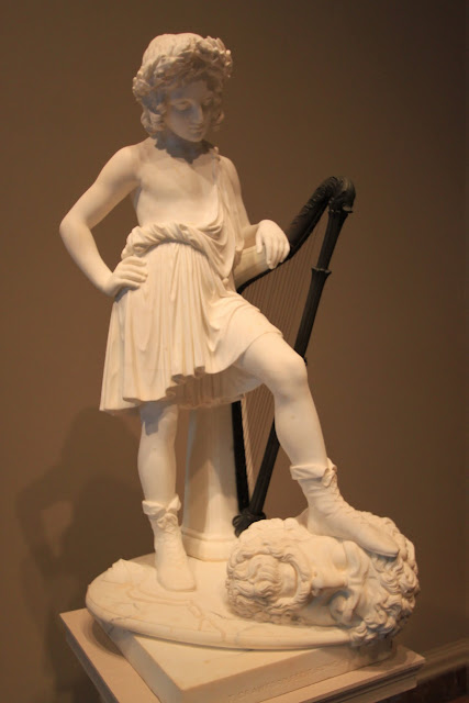 The sculpture of a little girl with her beautifully craved string lap harp at National Gallery of Art in Washington DC, USA