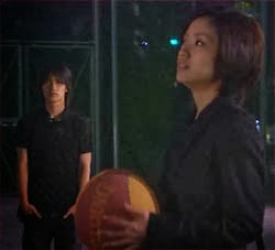 Misaki holding a basketball as she and Nakahara talk on the court.