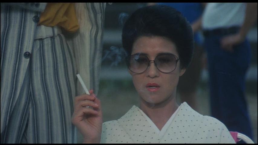 着物にサングラスにたばこで演技をする映画の中の十朱幸代