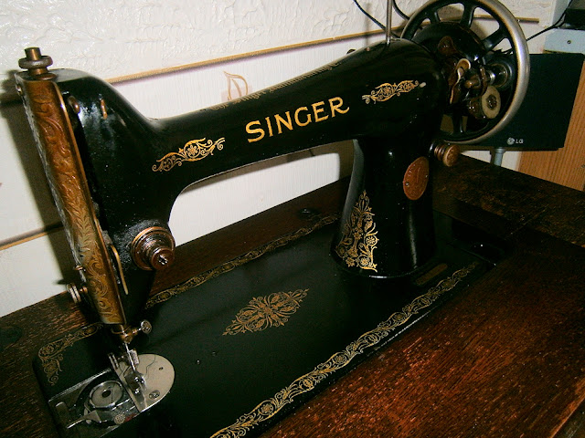 singer sewing machine black on table with draws