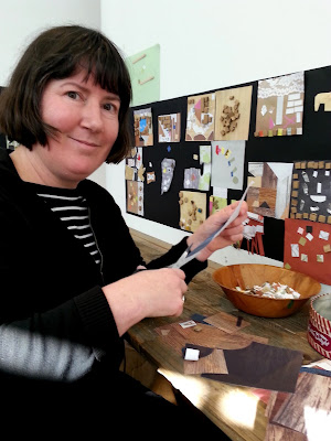 A woman cutting paper for her collage in the children's room at The Daylight Moon exhibition.