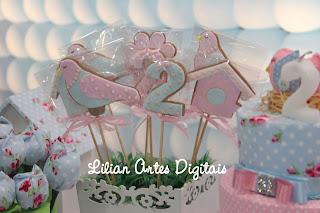 Foto do bolo e biscoito no tema de passarinho azul e rosa.