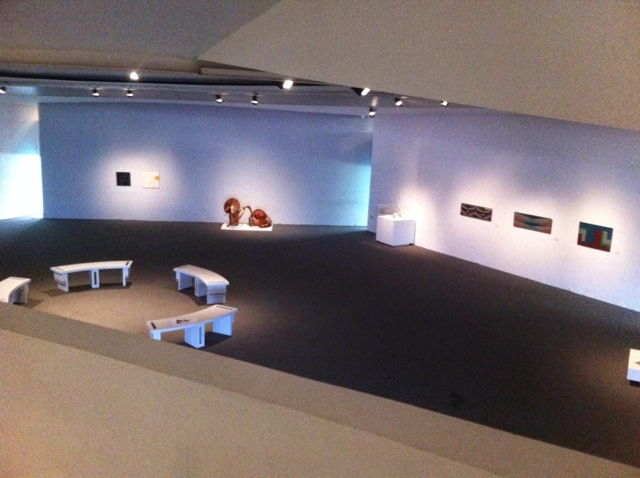Descrição da Foto: Imagem vista de cima do salão de exposição com paredes brancas, piso marrom, com iluminações direcionadas tanto para algumas obras de Ligia Clark, pinturas e esculturas, quanto bancos brancos, do lado esquerdo, área reservada as atividades do educativo.