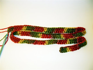1 row of the chunky scarf coiled up like a snake, colors are red, green, pink, and tan