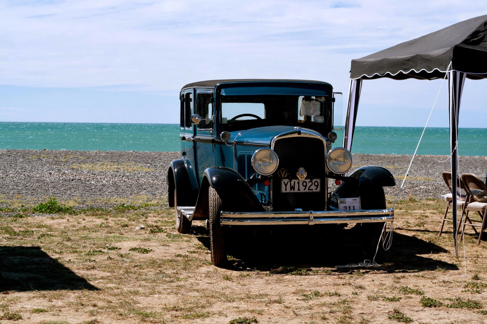 Vintage car sits on a beach.