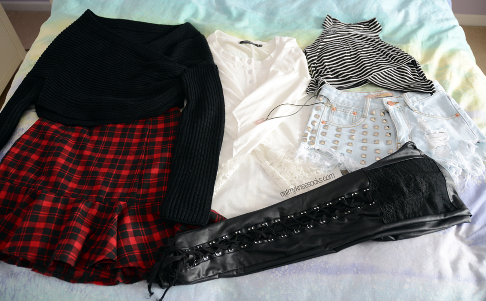 All the items I got from JollyChic this time, including a plaid skirt, cropped sweater, crop top, studded shorts, lace shirt, leather leggings, and crystal choker.