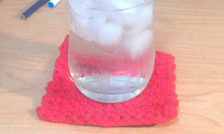 glass of ice water on crocheted red coaster