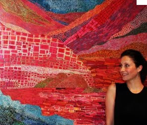 Galia Gluckman with one of her eco artworks - a warm landscape art piece created by using magazine paper clippings