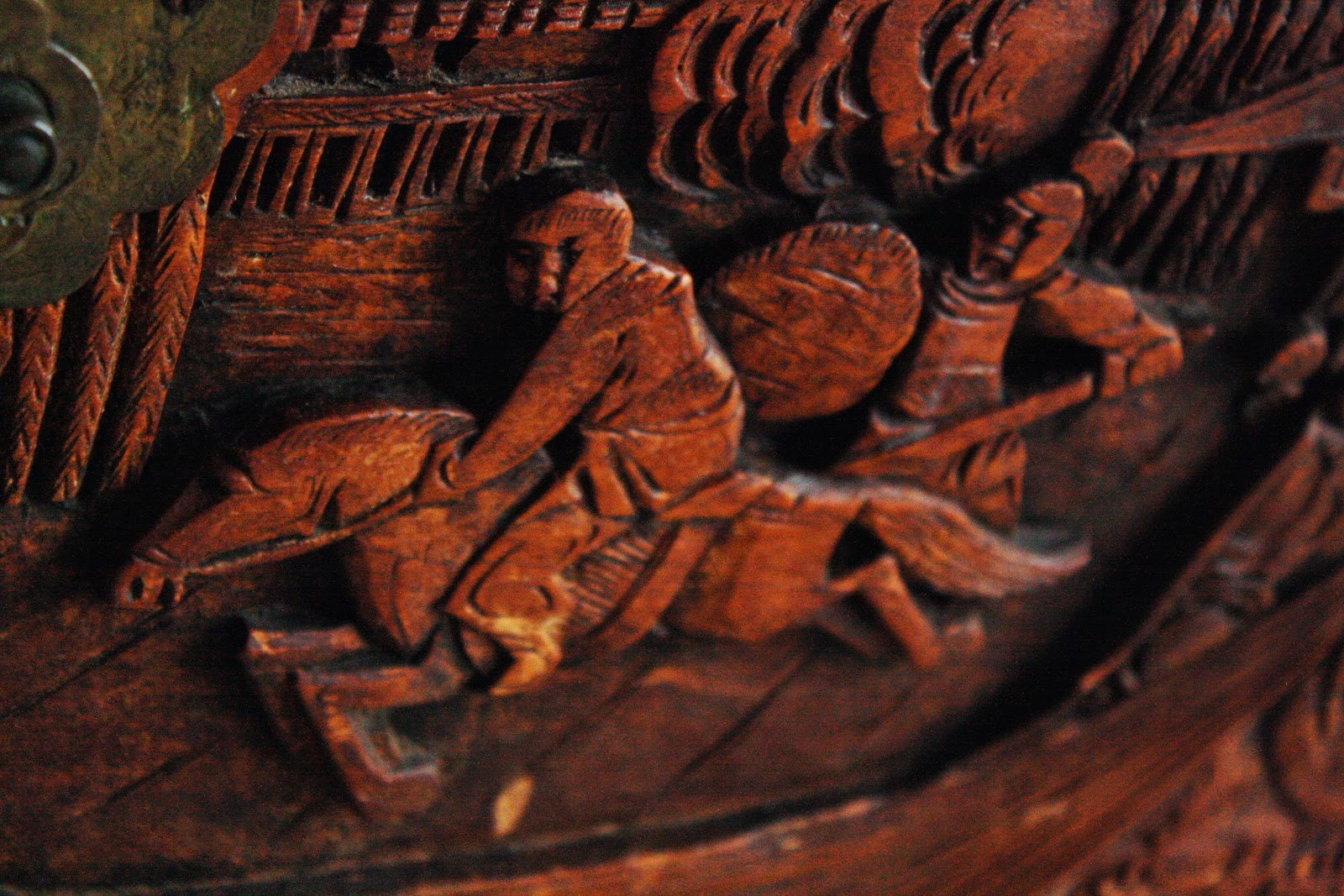 A battle scene carved into the side of a camphor wood chest.