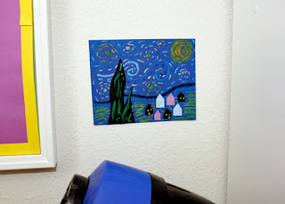 "Inspiration struck as Tessa worked on her original ""Starry Night,"" so I snatched a scrap from the trashcan and went to work. I hung my mini masterpiece, which is only a couple of inches tall, next to the school table. It makes me happy when I look at it for some reason."