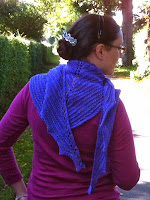A photograph of a person wearing a shawl knitted using my new pattern