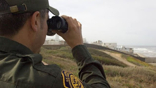 A U.S. Border Protection agent checks the border with binoculars.