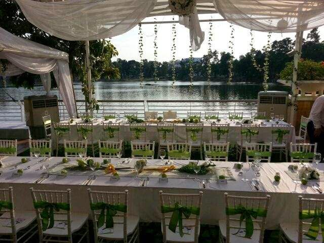 white chairs decorated with green sashes