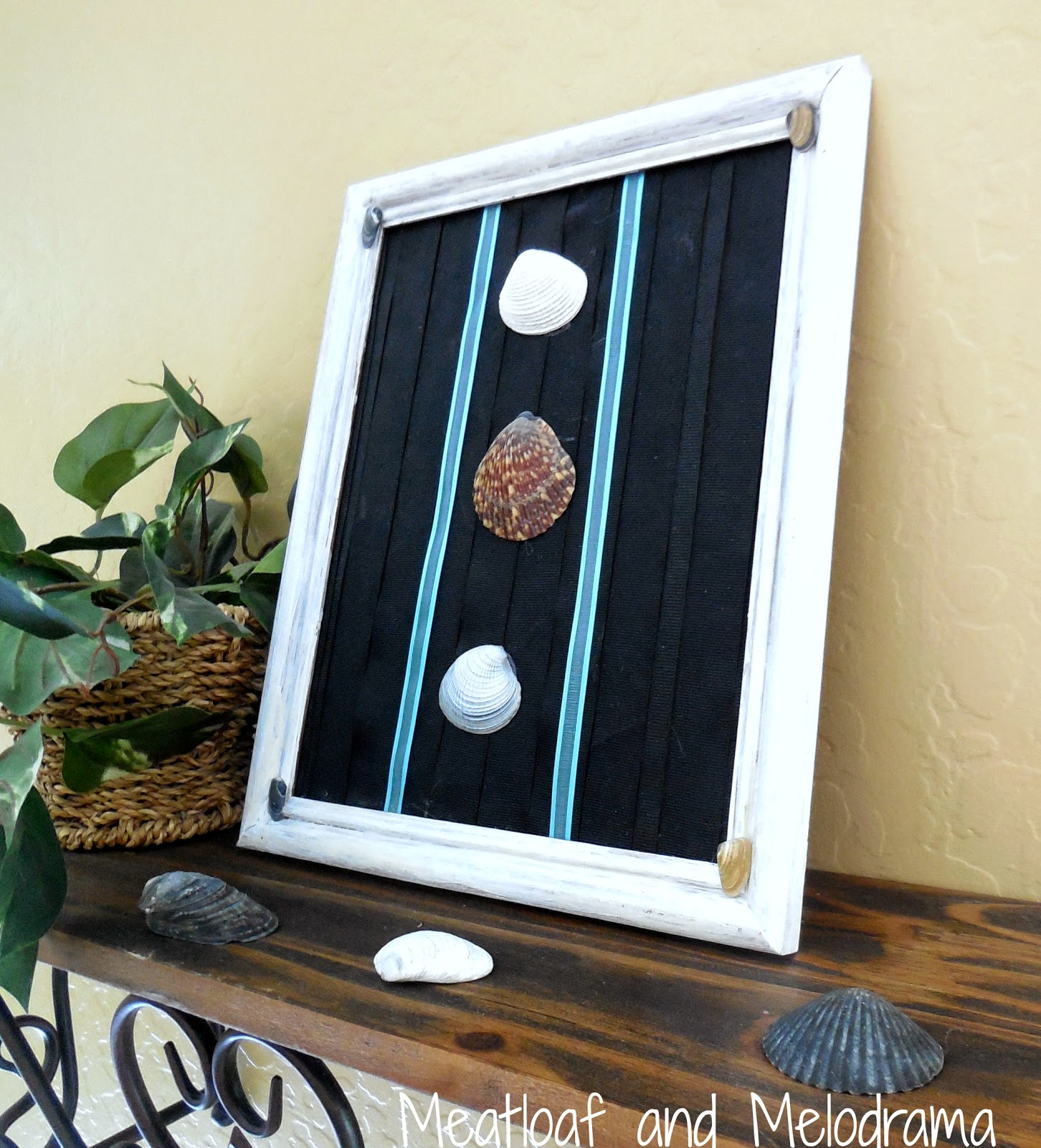 white picture frame with ribbons and seashells