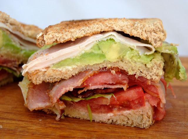 Sándwich casero con aguacate, tomate, bacon crujiente y pavo