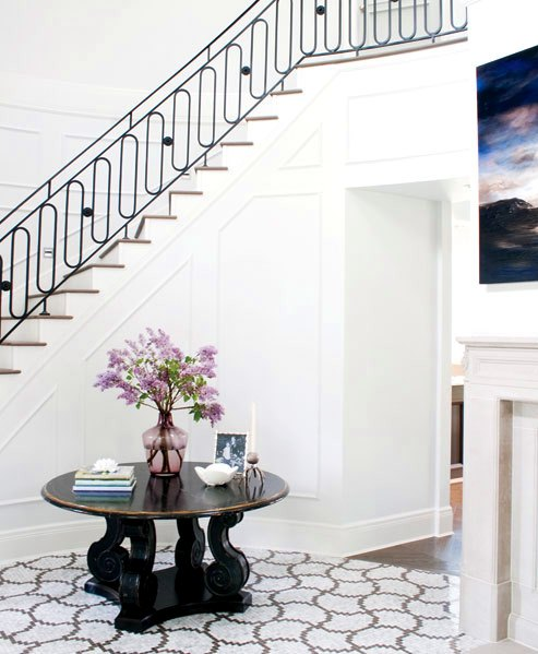 Foyer with grand staircase, a round dark wood table and marble mosaic tiles