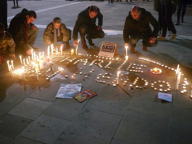 des personnes allument des bougies formant un 'charlie hebdo' en lettres lumineuses
