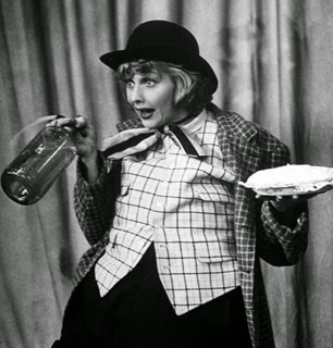 Lucy is dressed clown like and is folding a pie in one hand a squirting water bottle in the other.