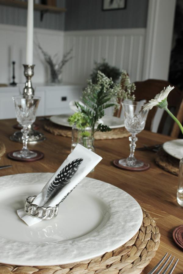 vårdukning, servetter med fjädrar, vita stora tallrikar, blommor i små vaser på bordet, blommor, kristallglas, tallriksunderlägg hampa,
