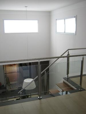 Visão do atelier para a sala de jantar e cozinha. As bandeiras de ventilação próximas ao teto oferecem a luminosidade natural para o interior da residência.