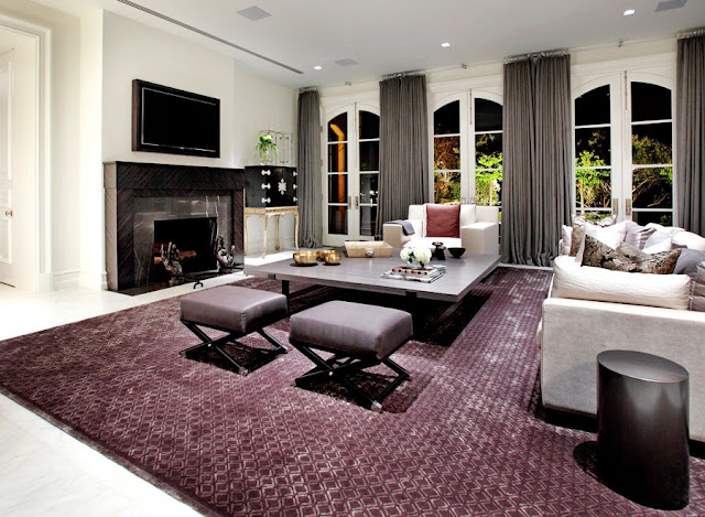 Den in a mansion on Harbor Island, in Newport Beach with french doors, gray floor length curtains, a large purple rug, gray coffee table, gray sofa and a large marble fireplace