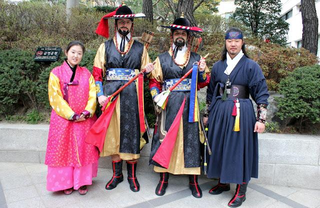 Extranjeros vestidos de guardias tradicionales de palacios coreanos