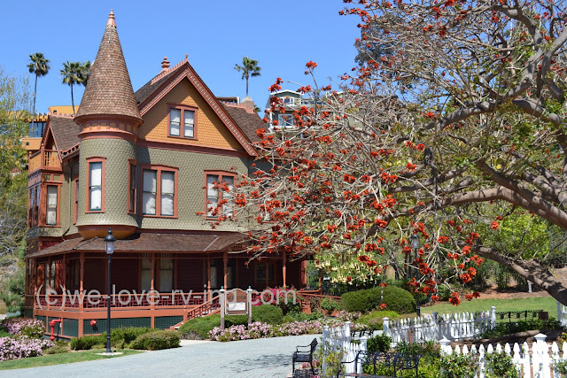 Home has classic victorian design with shingles, the corner tower and a veranda encircling it.