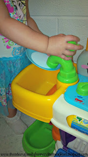 Washing dishes in a play kitchen
