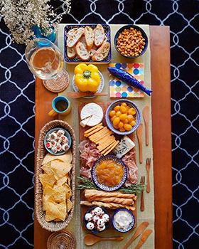 Uma tábua com comidinhas amarelas e louças azuis