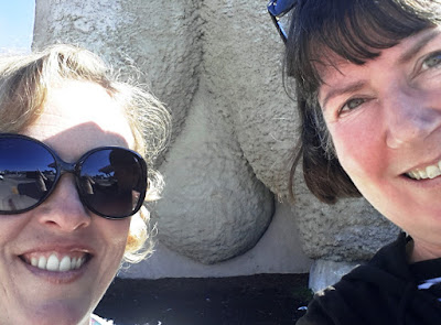 Two women posing in front of the bottom of the Giant Merino in Goulburn.