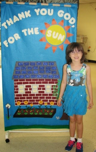 child stands beside completed banner showing our new solar array