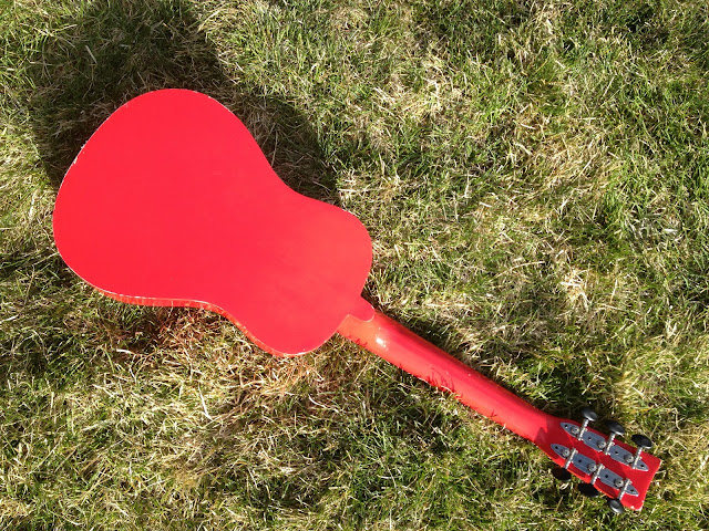 A red children's guitar laying in the sun face down in the grass.