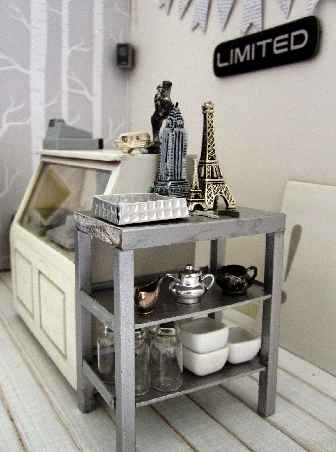 Counter area of a modern dolls' house miniature homeware shop in grey and white. On the counter is a cash register and two silver statues. To the right of the counter is a grey metal shelving unit displaying a selection of model buildings, a range of vintage silver jugs and a number of empty bottles and white bowls.