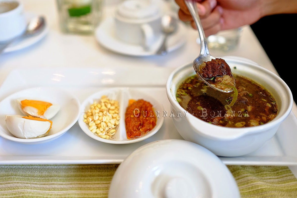 Rawon, a beef soup with dark brown (sometimes black) broth cooked with the notorious keluak fruit, served with sides such as shrimp crackers, mung bean sprouts, salted duck eggs, and sambal