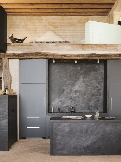 sleek modern black kitchen with slabs of basalt used for the backsplash and the island